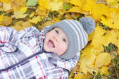 Lovely baby age of 1 year lying against yellow leaves — Stock Photo