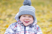 Funny baby age of 1 year puts out tongue outdoors in autumn — ストック写真
