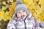 Baby age of 1 year lying against yellow leaves — Stock Photo