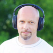 Stock Photo: Mlistening music outdoors in wireless headset