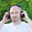 Stock Photo: Happy mlistening music outdoors in wireless headset