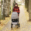 Woman walking in autumn park with baby buggy — Stock Photo