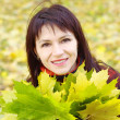 Portrait of smiling woman with maple leaves in autumn — Stock Photo