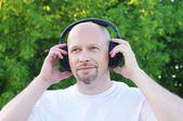 Música ao ar livre no fone de ouvido sem fio homem feliz — Fotografia Stock