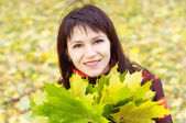 Portrait of smiling woman with maple leaves in autumn — Stock fotografie
