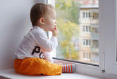 Baby age of 1 year looks out of window — Stock Photo