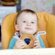 Smiling baby eating round cracknel on kitchen — Stock Photo #34822377