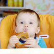 Funny baby boy eating round cracknel — Stock Photo #34822407