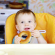 Happy baby eating round cracknel on kitchen — Stock Photo #34822421