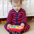 Stock Photo: Baby plays musical toy