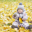Lovely baby age of 1 year with yellow leaf outdoors — Stock Photo