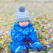 Sad baby boy sitting on yellow leaves in autumn — Foto de Stock