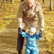 Father walking with baby son outdoors in autumn  — Stock Photo