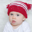 Portrait of lovely baby in red knitted hat — Stock Photo