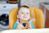 Smiling baby eating round cracknel on kitchen — Stock Photo