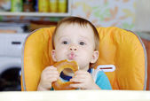 Funny baby boy eating round cracknel — Stock Photo