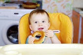 Happy baby eating round cracknel on kitchen — Stock Photo