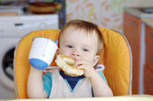 Baby with round cracknel and cup of tea — Stock Photo