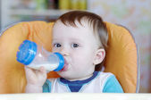 Lovely baby drinking milk from a small bottle — Stock Photo