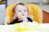 Lovely baby eating corn curls — Stock Photo