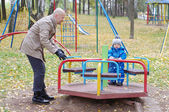 Father plays with baby son of 1 year in autumn on playground — Stock Photo