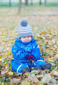 Sad baby boy sitting on yellow leaves in autumn — Stock Photo
