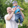 Happy father and baby son walking outdoors — Stock Photo