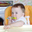 Lovely baby age of 11 months with spoon on kitchen — Stock Photo #34860483