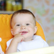 Lovely baby sitting on baby chair on kitchen — Stock Photo