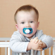 Baby with dummy in white bed — Stock Photo #34860817