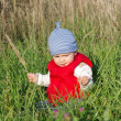 Baby in red waistcoat sitting on grass outdoors — Stock Photo