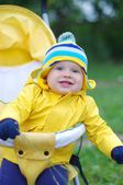 Smiling baby in yellow jacket on baby carriage — Stock Photo