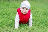 Lovely baby in red waistcoat creeps on grass — Stock Photo