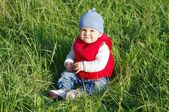 Lovely baby in red waistcoat on grass outdoors — Stock Photo