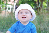Portrait of smiling baby in white hat — Stock Photo