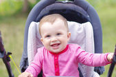 Happy baby on baby carriage in summer — Stock Photo