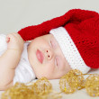 Sleeping baby age of 2 months in a New Year's hat — Stock Photo #34874839