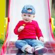 Baby on slide wiht dandelion in hand — Stock Photo