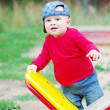 Stock Photo: Baby boy stands by teeter-totter