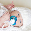 Stock Photo: Portrait of lovely newborn with dummy in white knitted hat