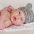 Lovely newborn in gray hat — Stock Photo