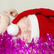 Lovely sleeping baby in New Year's hat among spangle — Stock Photo #34874755