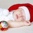 Sleeping baby in New Year's hat and Christmas-tree decoration — Stock Photo