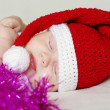 Sleeping baby in New Year's hat among spangle — Stock Photo #34874763