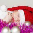 Sleeping baby-santa among christmas decoration — Stock Photo