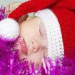 Sleeping baby in New Year's hat waiting gifts — Stock Photo