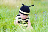 Upset baby in bee costume on the meadow — Stock Photo