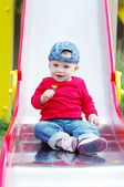 Baby on slide wiht dandelion in hand — Stock Photo