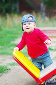 Baby boy stands by teeter-totter — Stock Photo