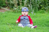 Lovely baby age of 10 months sitting on grass in park — Stock Photo